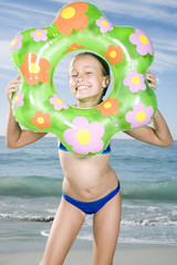 A young girl on the beach with rubber ring