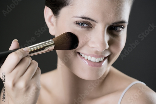 Woman applying blusher or bronzer on her face