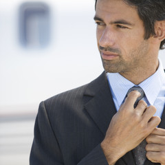 A businessman standing by a plane