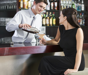 A barman pouring a cocktail for a customer