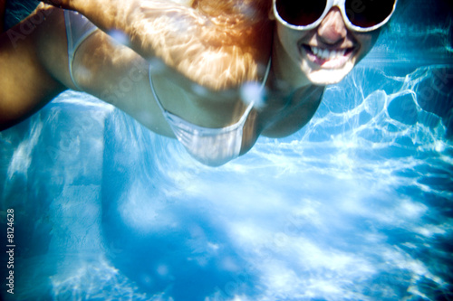 young woman underwater smiling for camera