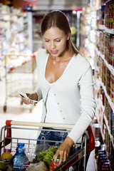 Woman putting shopping into a supermarket trolley