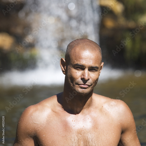 Portrait of a young man near a waterfall