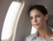 A businesswoman listening to music on a flight