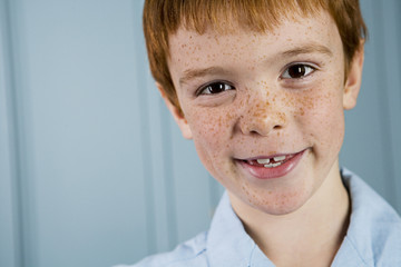 portrait boy with ginger hair and freckles smiling