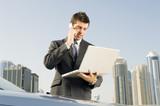 A businessman talkingon a mobile phone holding a laptop