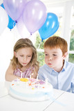 two children blowing out candles on birthday cake