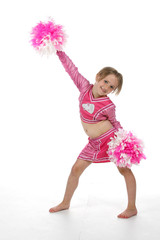 Cute girl in pink cheerleader outfit holding pompoms