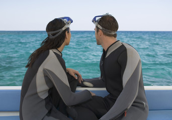 A couple sitting on a boat preparing to go scuba diving