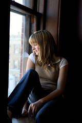 Pretty teen sitting on a window sill.