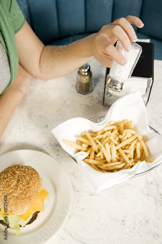 Close up of a girl putting salt on her fries