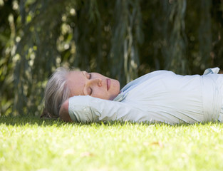 A senior woman asleep in the garden