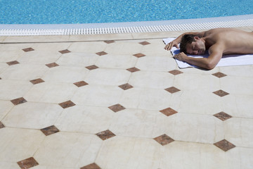 A man sunbathing by a pool