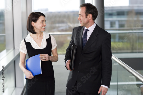 Male and female business colleagues chatting in office building
