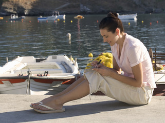 A woman sitting by a harbour writing a postcard