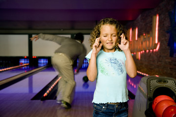 Father and daughter bowling, daughter crossing her fingers for good luck