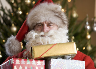 Father Christmas/Santa Claus holding a pile of presents