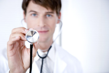 Male doctor holding a stethoscope towards the camera