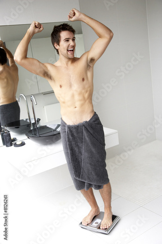 Young man standing on bathroom scales