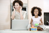 Stressed mother working from home while daughter plays a toy drum