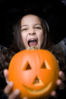 Girl in costume at a Hallowe'en party, holding a pumpkin with a carved face