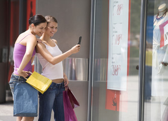 Two young women looking in a shop window