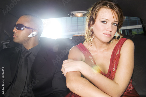 A woman sitting in the back of a car with her security guard
