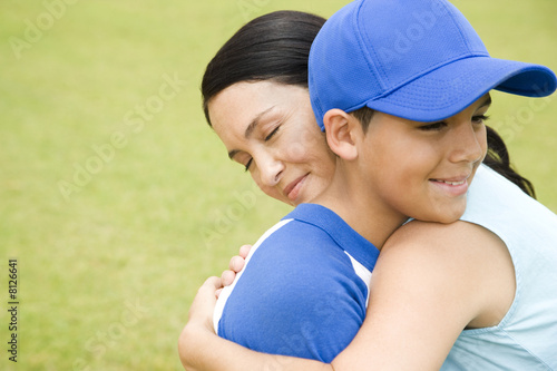 Mother hugging son in baseball gear