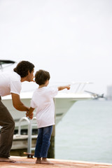 father and son pointing at sea from dock