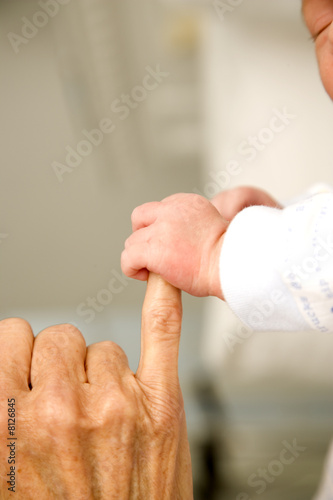 A baby's hand holding their grandparent's finger