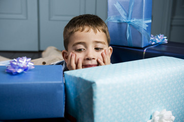 little boy looking at his presents