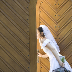 A bride looking through the church doors