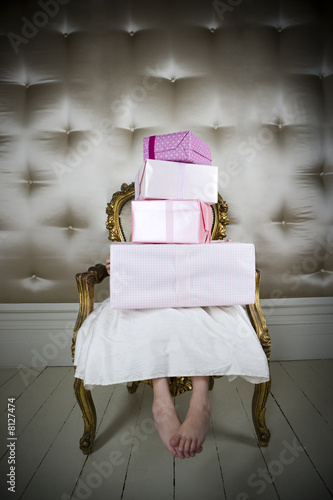 Little girl in a party dress holding a stack of birthday presents