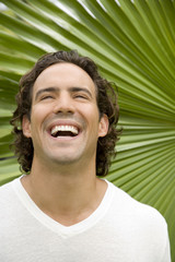 Portrait of a laughing adult man in a tropical garden.