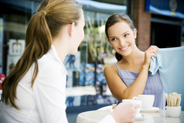 Woman showing clothes purchase to her friend over coffee at a pavement cafe
