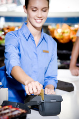 Portrait of a supermarket checkout assistant using a credit card machine