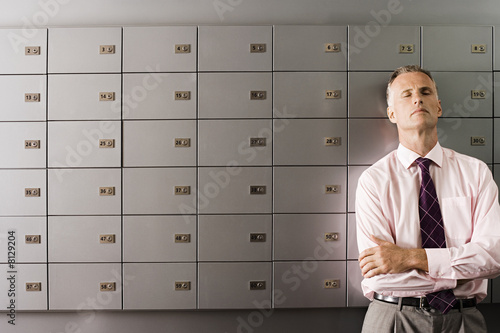 Mature businessman standing in front of row of lockers, arms folded, eyes closed, leaning back