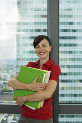 Businesswoman standing beside office window, holding green folder, smiling, portrait
