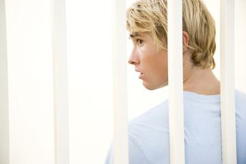 Portrait of a young man behind bars