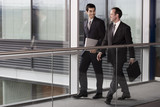 Two businessmen walking along in modern office building