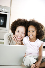 Mother and daughter with laptop in the kitchen at home