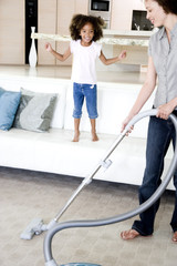 Mother vacuuming while young daughter watches