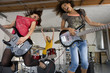 Three teenage girls (15-17) in garage band, two girls playing electric guitar in foreground