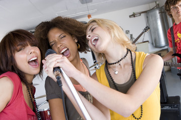 Three teenage girls (15-17) singing in garage band