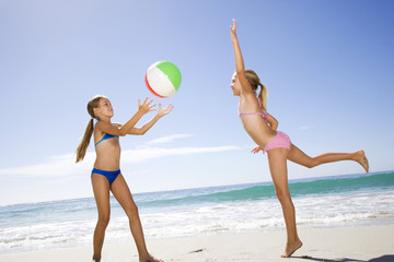 Two young girls playing on the beach