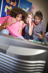 Three teenage friends (15-17) watching television with scared expressions on faces, television in foreground