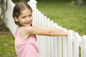 little girl standing by picket fence