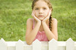 little girl leaning on fence looking sad