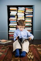 little boy sitting on the floor reading