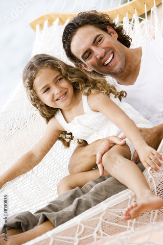 father and daughter sitting in a hammock